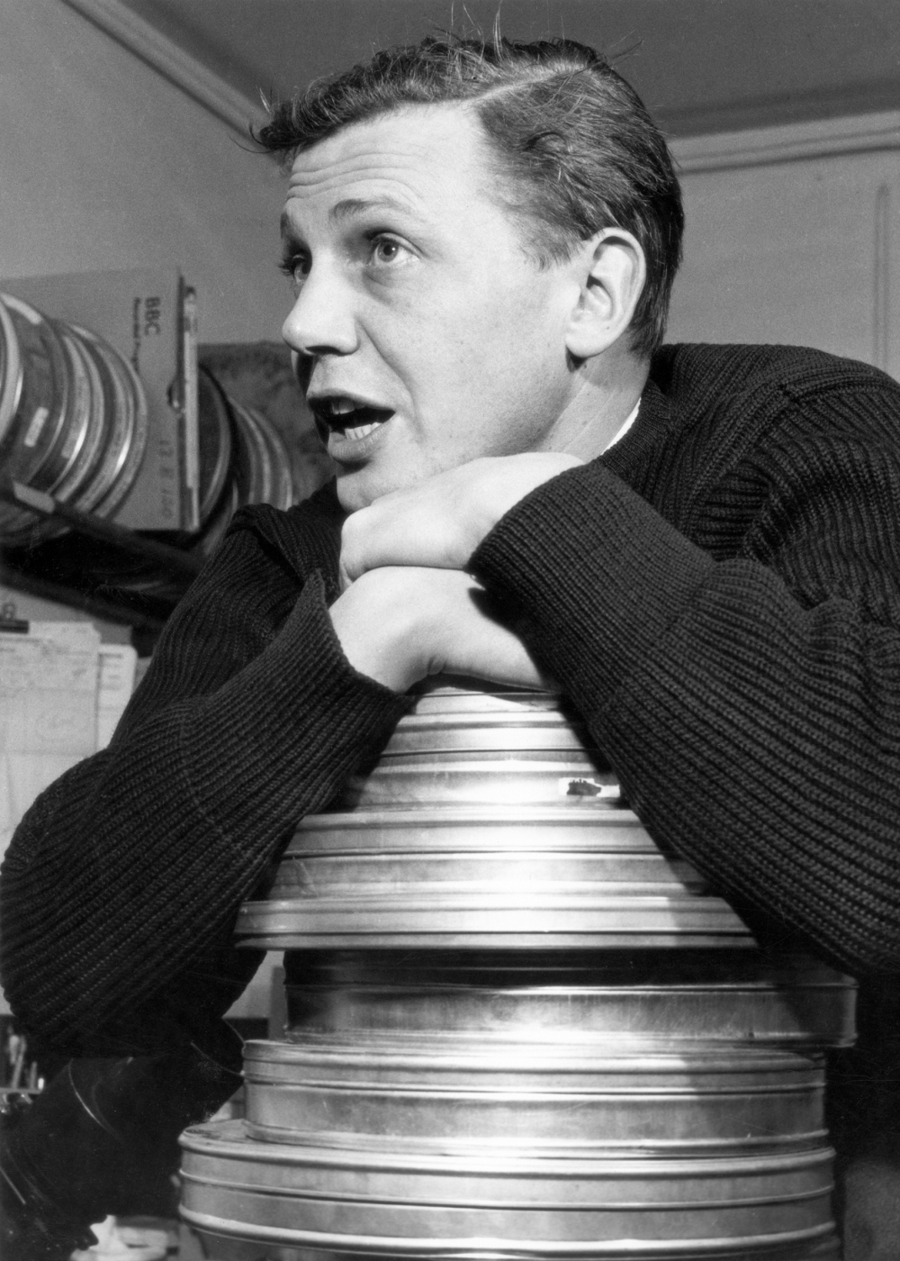 Archvie still: Sir David Attenborough leans on film cans. Circa 1962 when David was Head of the Travel and Talks Department.